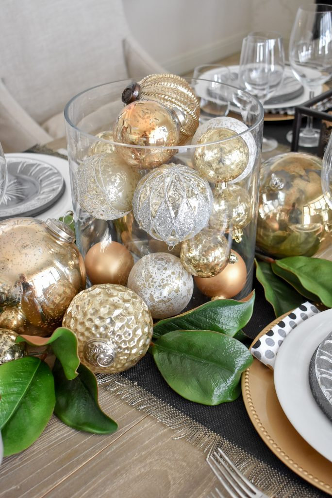 Centerpiece with Christmas ornaments on a Modern Glam Table Setting with Black and Gold and Silver