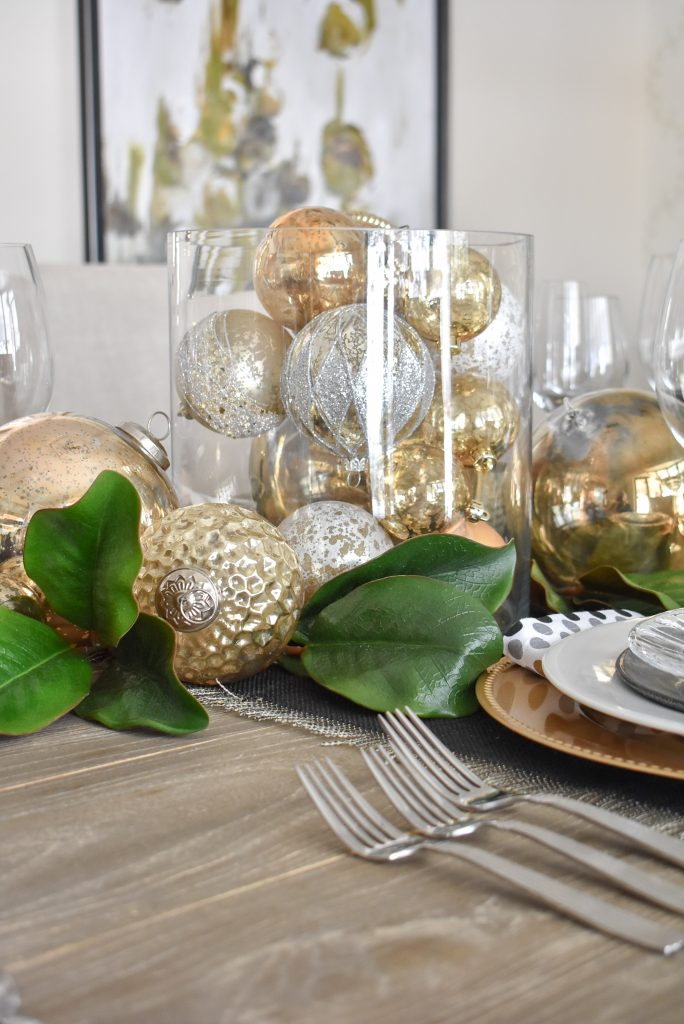 A Christmas Ornament Centerpiece on Modern Glam Table Setting with Black and Gold and Silver