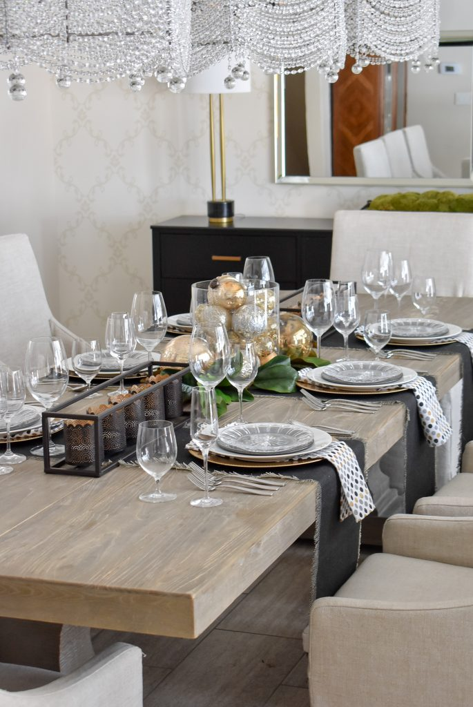 A Modern Glam Table Setting with Black and Gold and Silver in a dining room