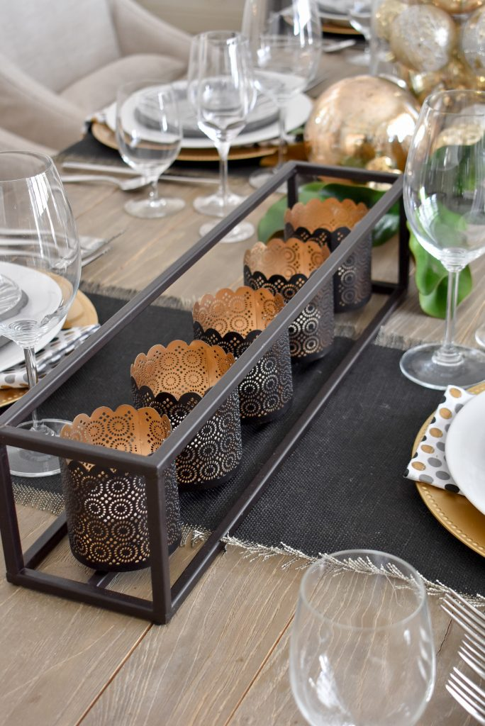 Black votive holders on a Modern Glam Table Setting with Black and Gold and Silver