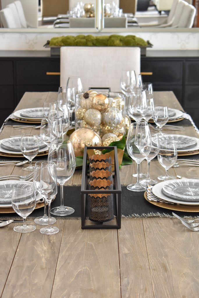 A Festive Modern Glam Table Setting with Black and Gold and Silver