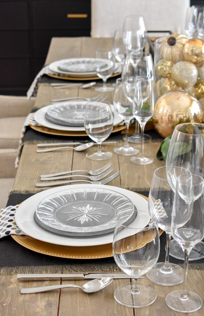 Place settings on a Modern Glam Table Setting with Black and Gold and Silver on a dining room table