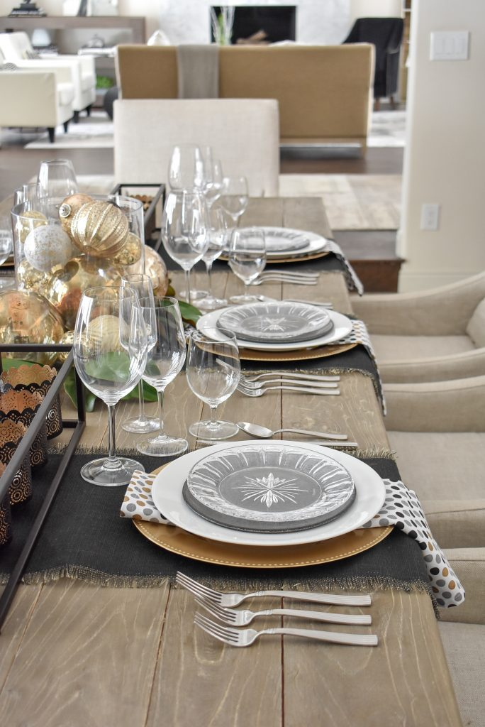 Place settings on a Modern Glam Table Setting with Black and Gold and Silver in a dining room
