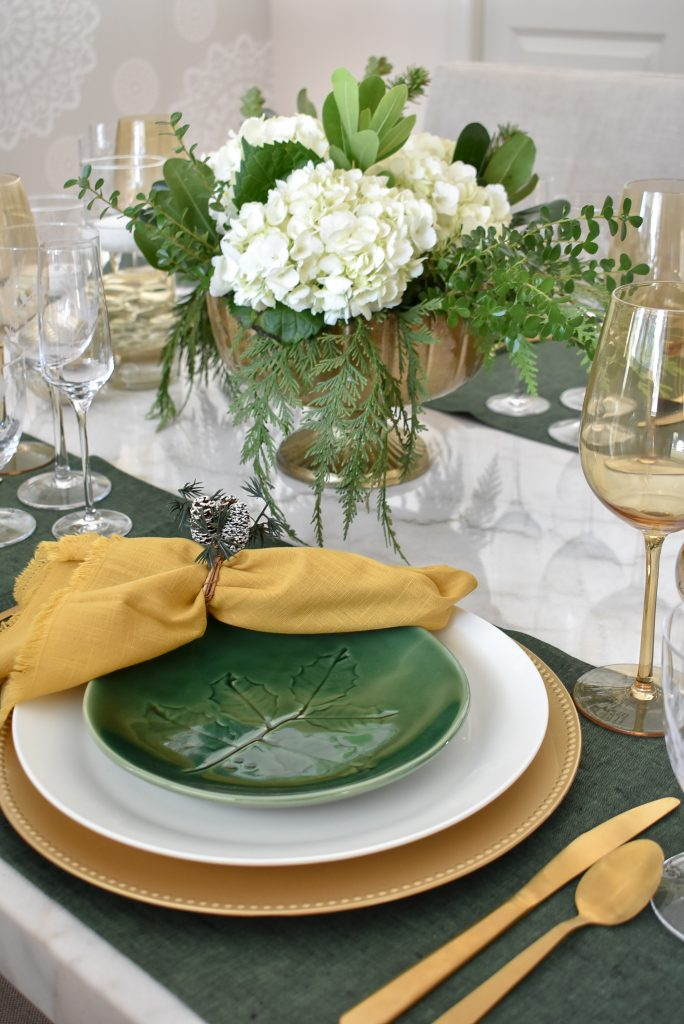 Simple White and Evergreen Christmas Centerpieces on a white marble table