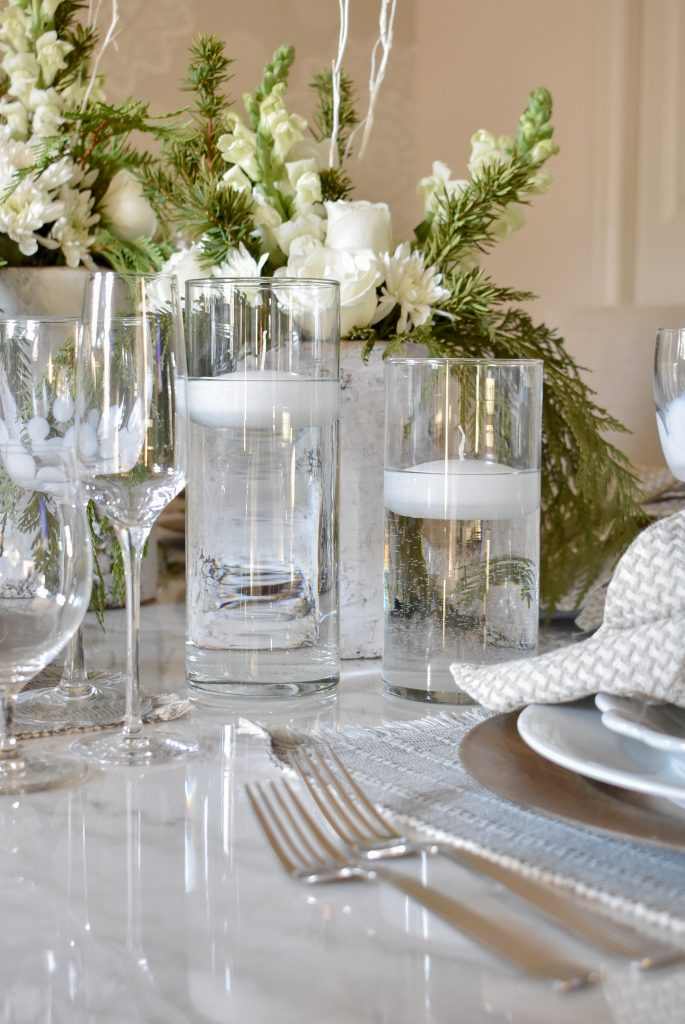 Vases with floating candles on aWhite Woodsy Christmas Table Setting