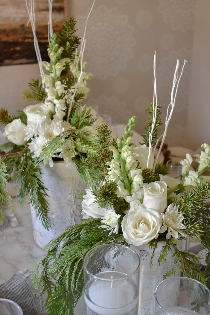 Centerpieces on a White Woodsy Christmas Table Setting