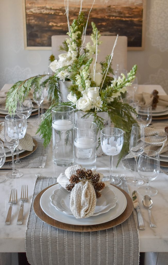 A White Woodsy Christmas Table Setting on a white marble table