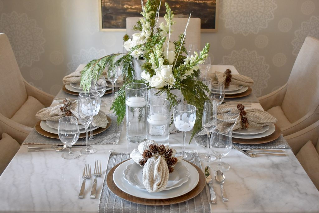 A White Woodsy Christmas Table Setting on a marble table