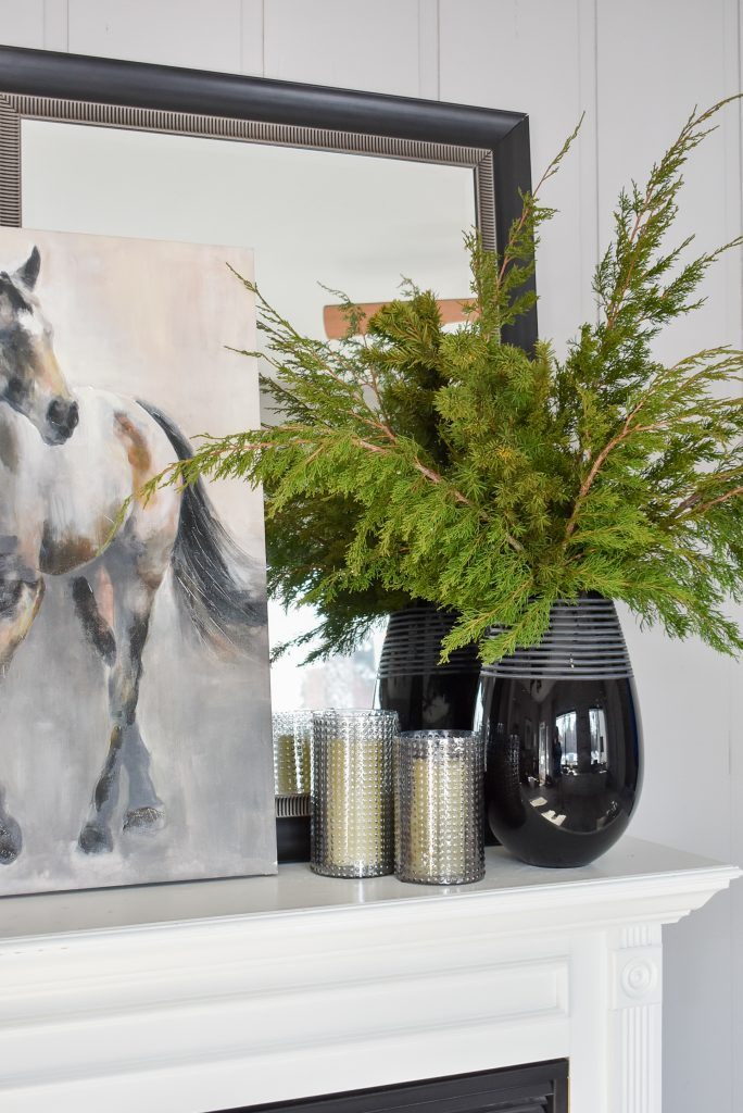Winter Evergreens in a black vase on a mantel to Transition your Decor from Christmas to Winter