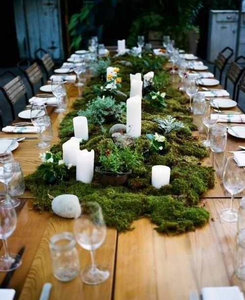 A large moss centerpiece on a rustic wood table