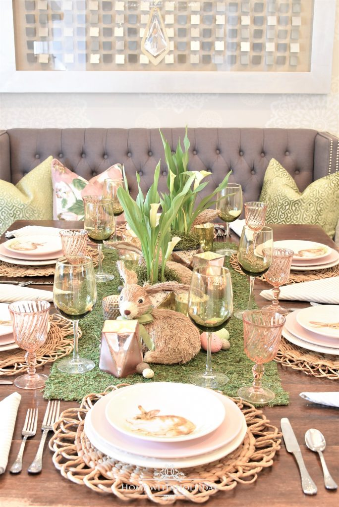 A green and blush pink Easter Table Setting with a moss centerpiece