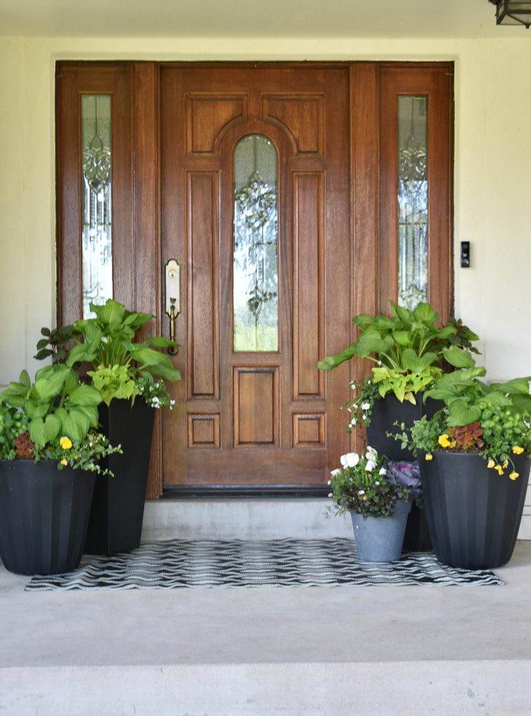 Several planted pots on a front porch