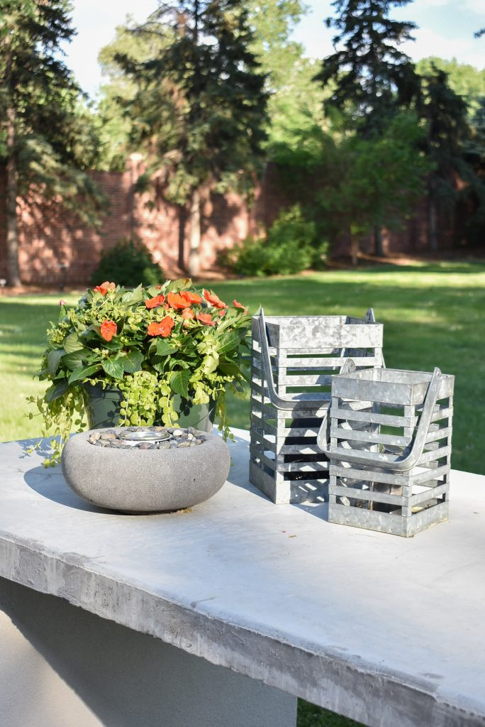 A patio kitchen island with flowers and accessories
