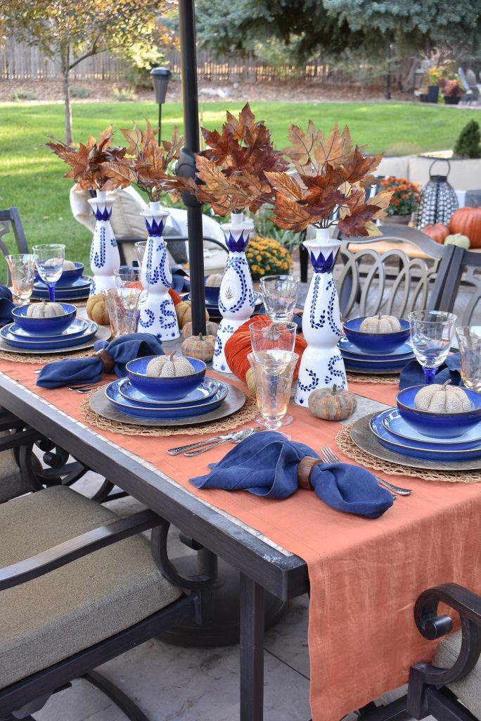 Centerpiece with Azul Tequila Bottles on a Blue and Orange Alfresco Dining Tablescape for Fall