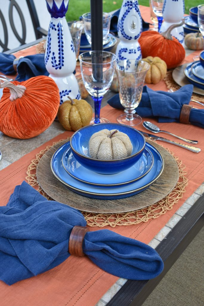 The place settings on a Blue and Orange Alfresco Dining Tablescape for Fall