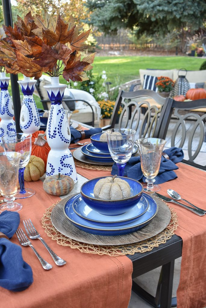 A Blue and Orange Alfresco Dining Tablescape for Fall with Pumpkins