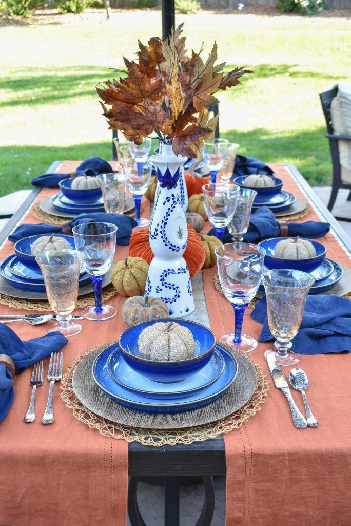 A blue and orange alfresco tablescape for fall
